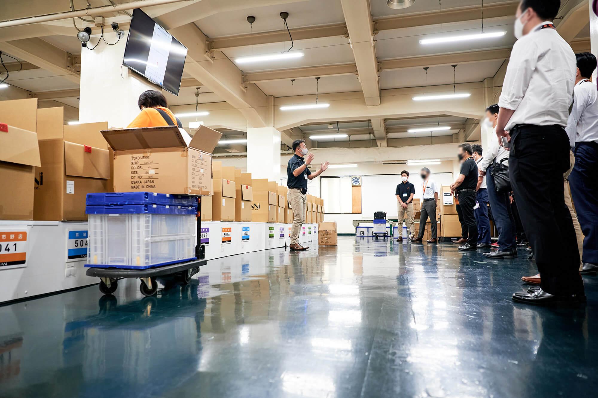 倉庫内の開けたスペースにて、大勢のお客様を前に説明をしているスタッフの様子
