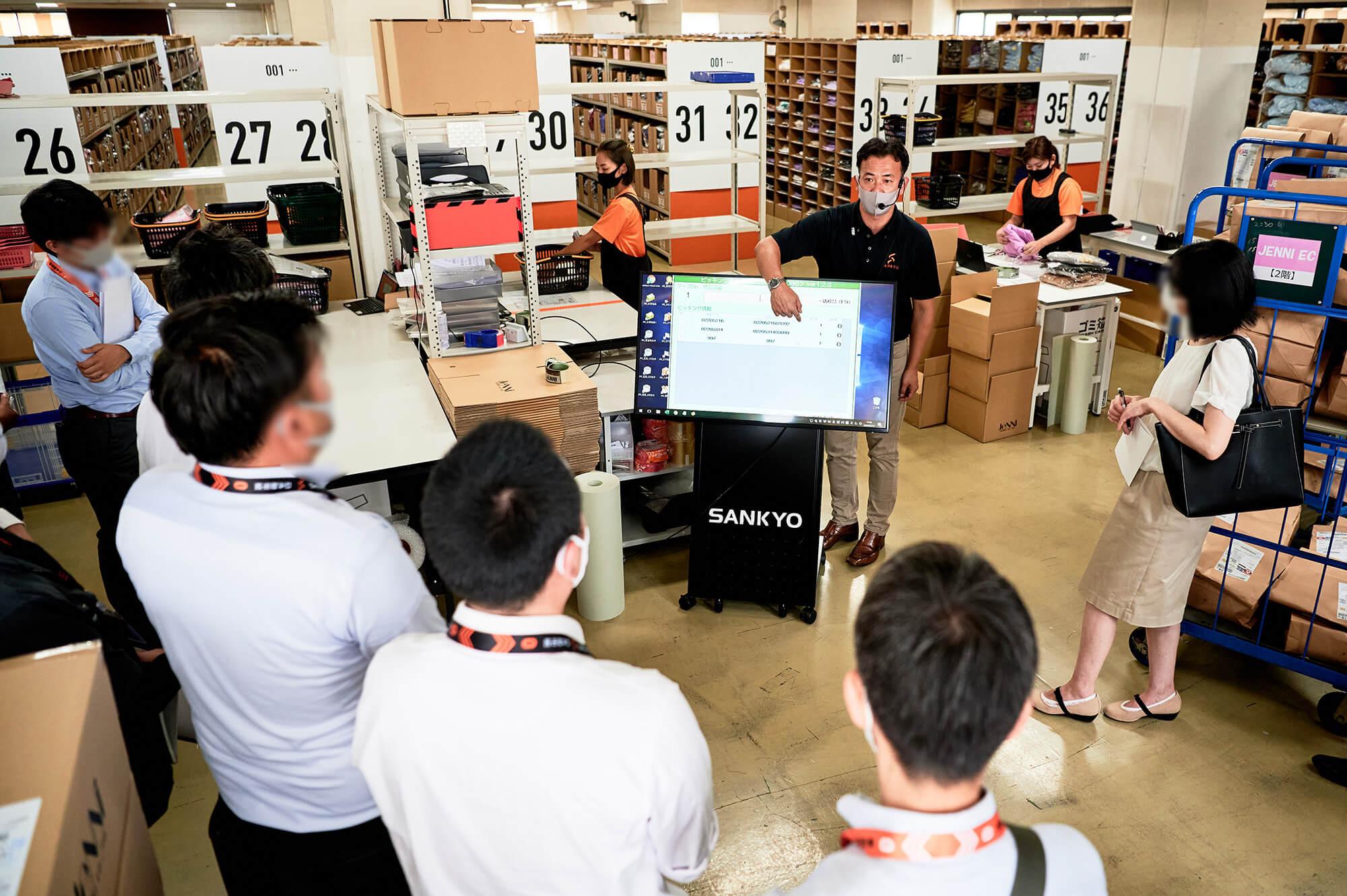 倉庫内で作業をしているスタッフを背景に、大勢のお客様に対し、キャスター付きの大きなモニターを使い説明をしているスタッフの様子