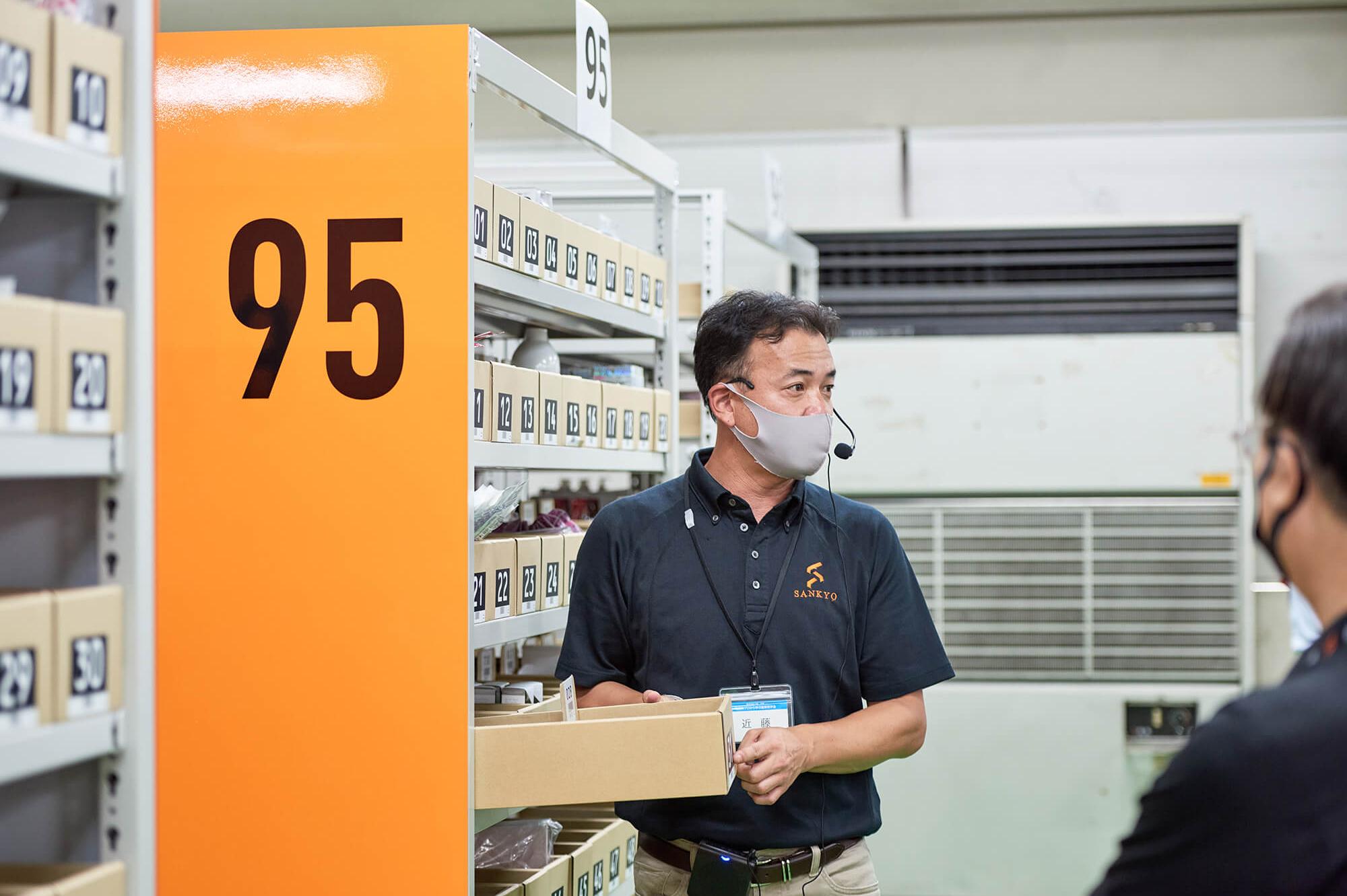 倉庫内にて、お客様に対しラック内の管理番号を指さして説明をするスタッフの様子